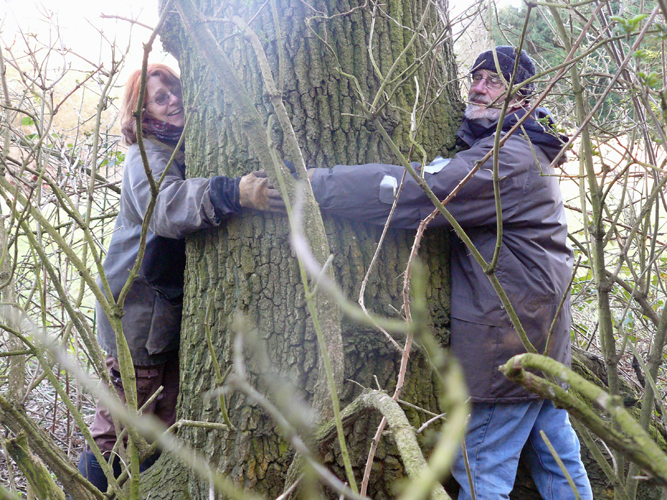 Hugging a large oak tree in our woodland